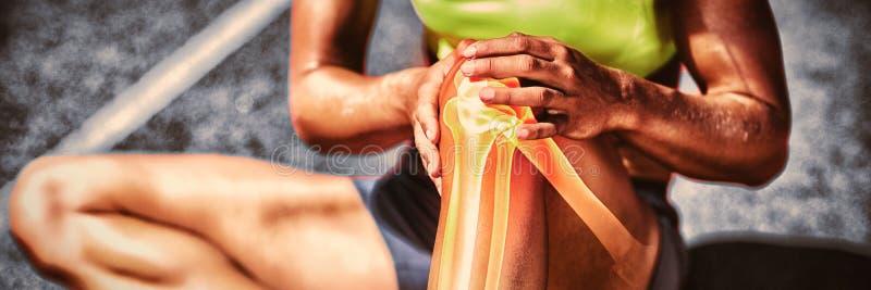 Lage sectie die van sportvrouw aan kniepijn lijden stock foto's
