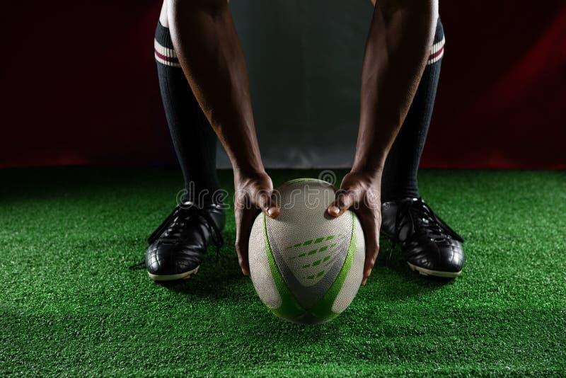 Lage sectie van de holdingsbal van de rugbyspeler terwijl status tegen Italiaanse Vlag stock fotografie