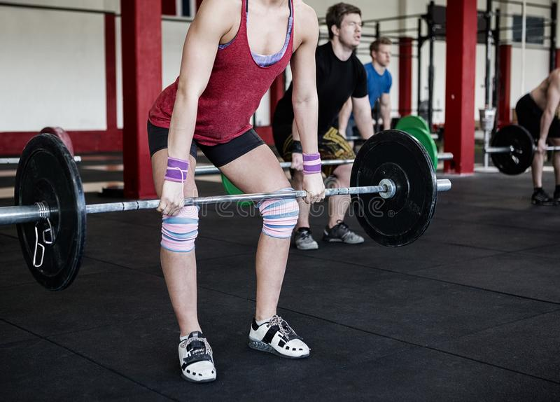 Lage Sectie van Vrouwelijke Trainer Lifting Barbell stock fotografie