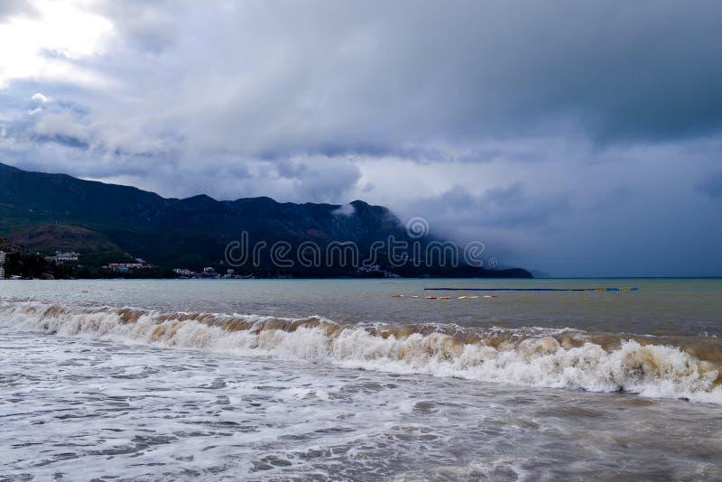 Lage wolken over de kustgolven van troebel water Het strand van Montenegro in regenachtig weer Het overzees en de bergen van Mont royalty-vrije stock foto's