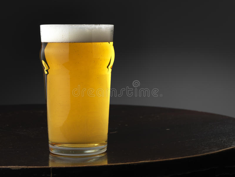 Lagegr and Beer. Glass of beer on a pub tabletop royalty free stock images