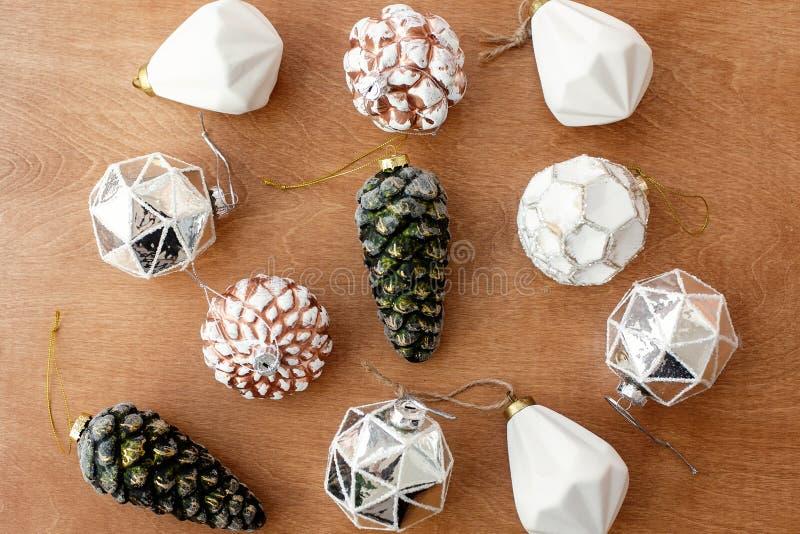 Lagen de Kerstmis moderne ornamenten op houten vlakte als achtergrond Modieuze uitstekende glassnuisterijen en denneappels, vakan stock afbeelding