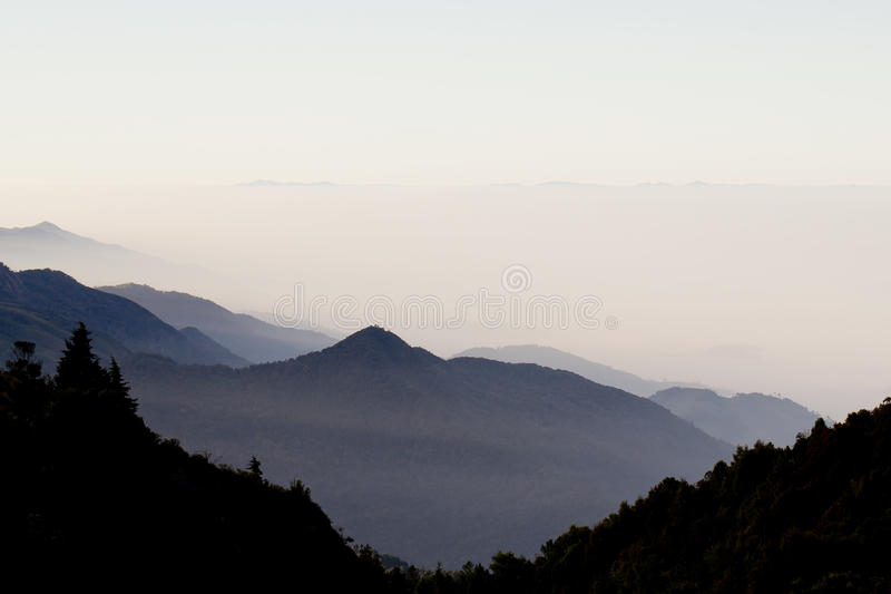 Lagen van bergen en mist bij zonsopgang royalty-vrije stock fotografie