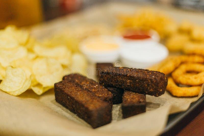 Lageröl och mellanmål på trätabellen Muttrar chiper, jordnöt, rostat bröd, smällare Aptitretaresnabbmat Hantverköl Beerboard arkivbild