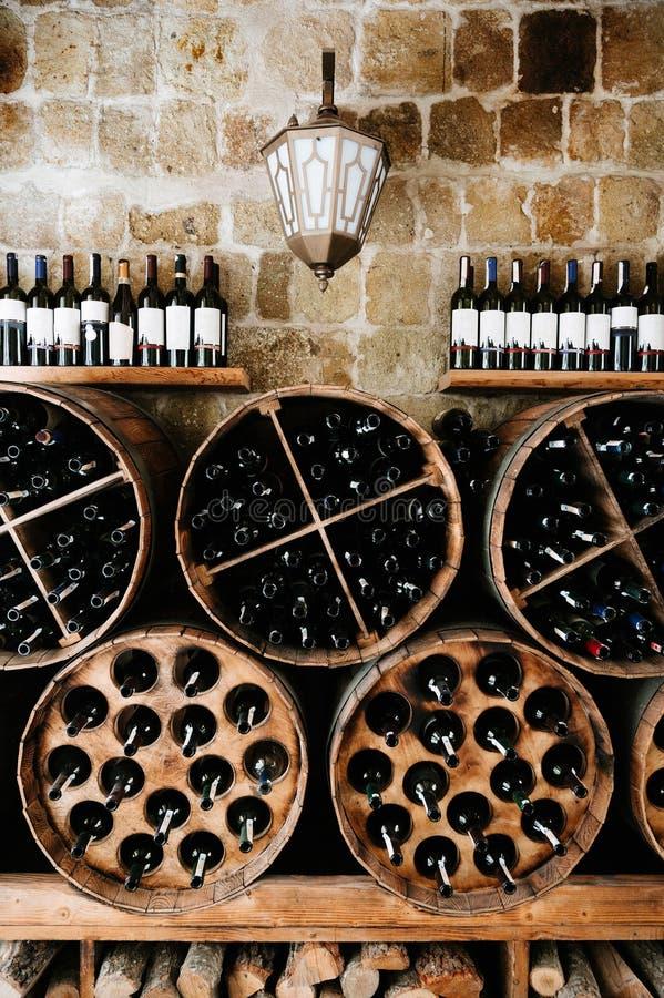 Lager av gamla flaskor av vin i källare close upp royaltyfria foton