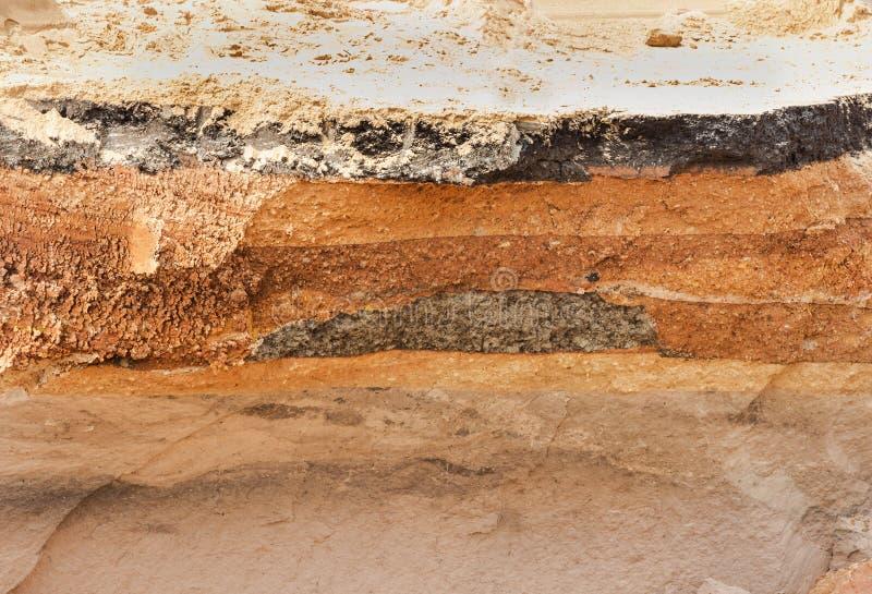 Lager av jord under den skadade asfaltvägen arkivbild