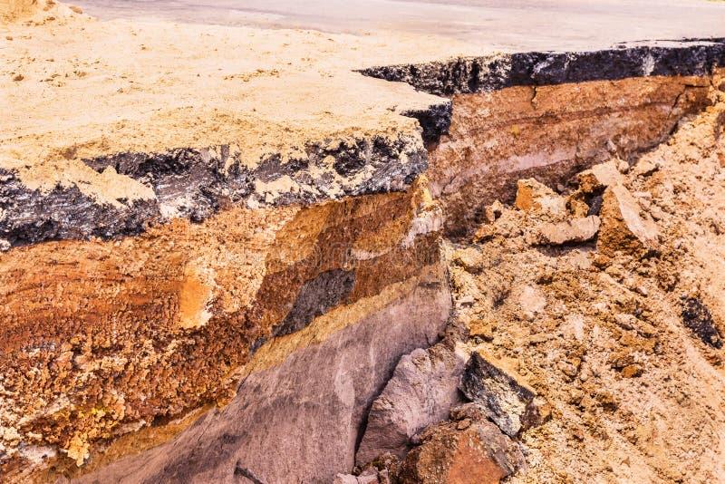 Lager av jord under den skadade asfaltvägen fotografering för bildbyråer