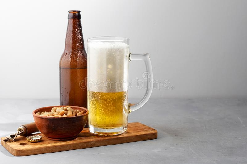 Lager beer pouring in glass and bottle with salted peanuts. On gray concrete background. Close up view with copy space stock photo