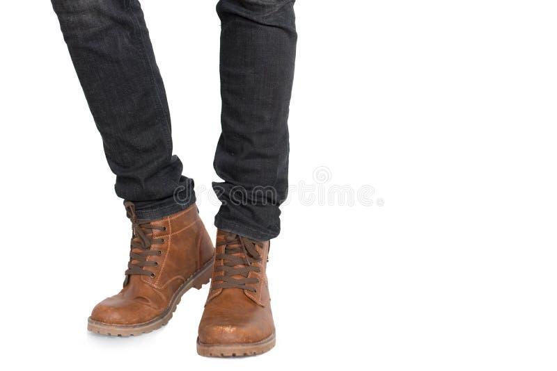 Lager - de helft van Mensenbeen en voet die jeans en schoenen op ge?soleerde witte achtergrond dragen Manier en mensenconcept Del stock afbeelding