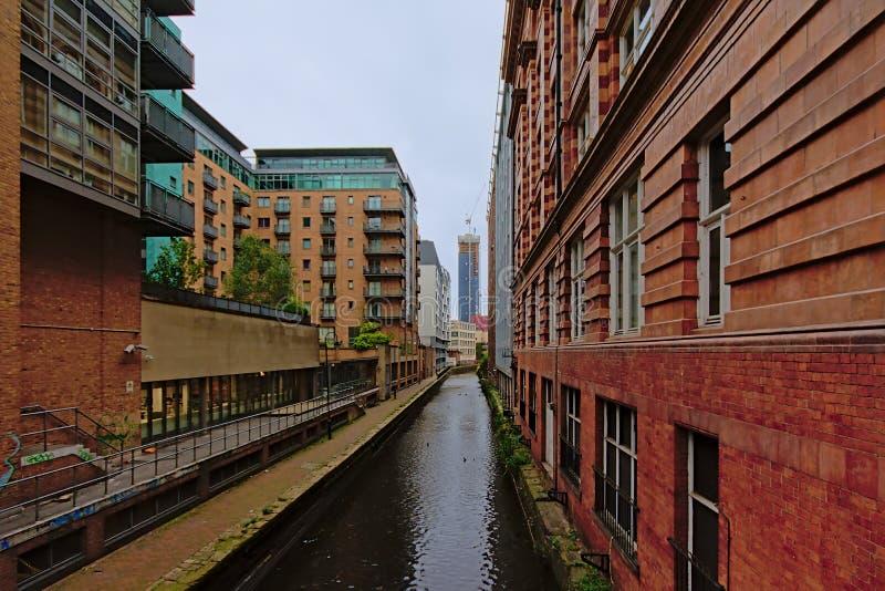 Lager och hyreshusar längs en kanal i Manchester arkivbilder