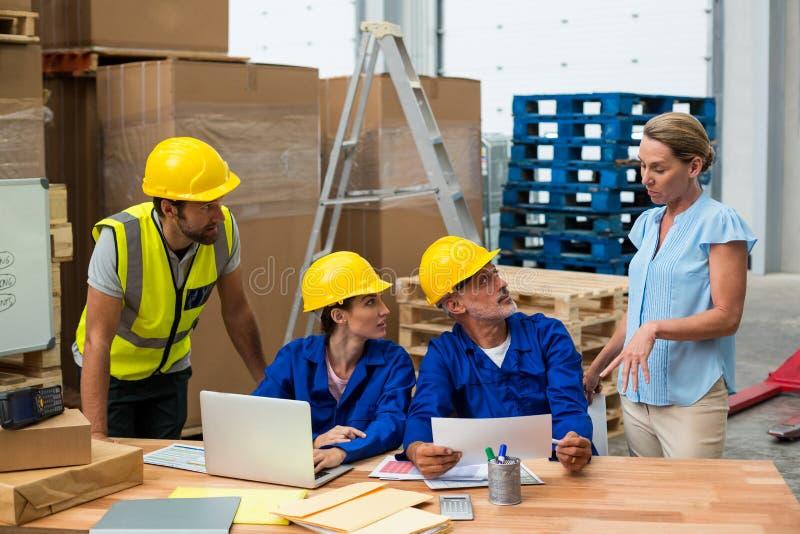 Lagerarbeitskräfte, die mit Manager sich besprechen stockfoto