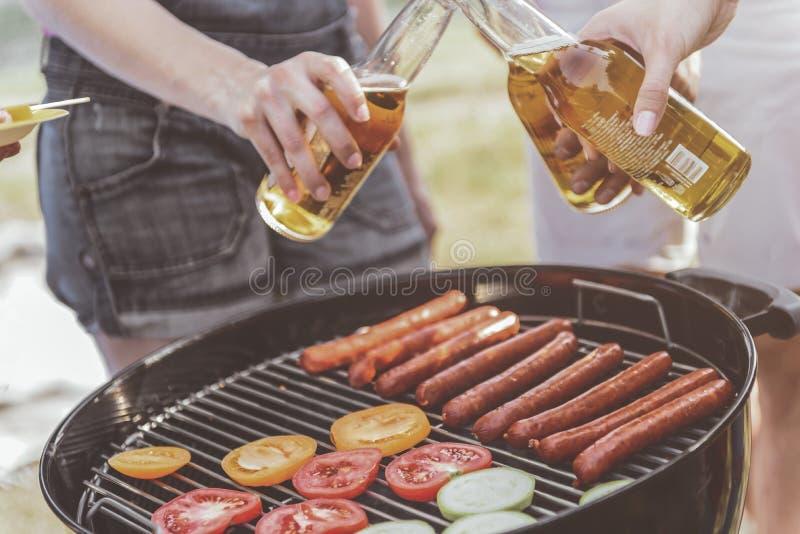 Lagerbewohner, die Bier mit Grill trinken lizenzfreie stockbilder
