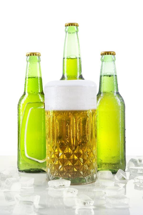 Lagerbier met schuim in het glas en de flessen stock foto's