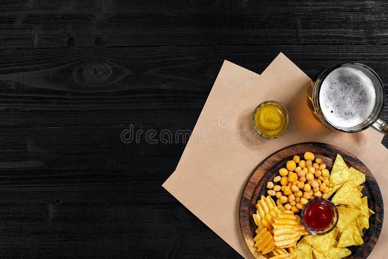 Lagerbierbier en snacks op zwarte houten lijst Noten, spaanders Hoogste Mening met Copyspace stock foto's