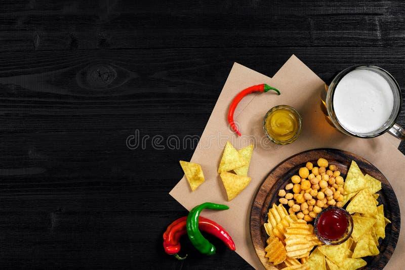 Lagerbierbier en snacks op zwarte houten lijst Noten, spaanders Hoogste Mening met Copyspace stock foto