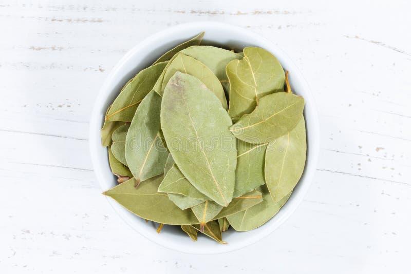 Lagerbladen lämnar kryddaörten från träbräde för ovannämnd bunke royaltyfri fotografi