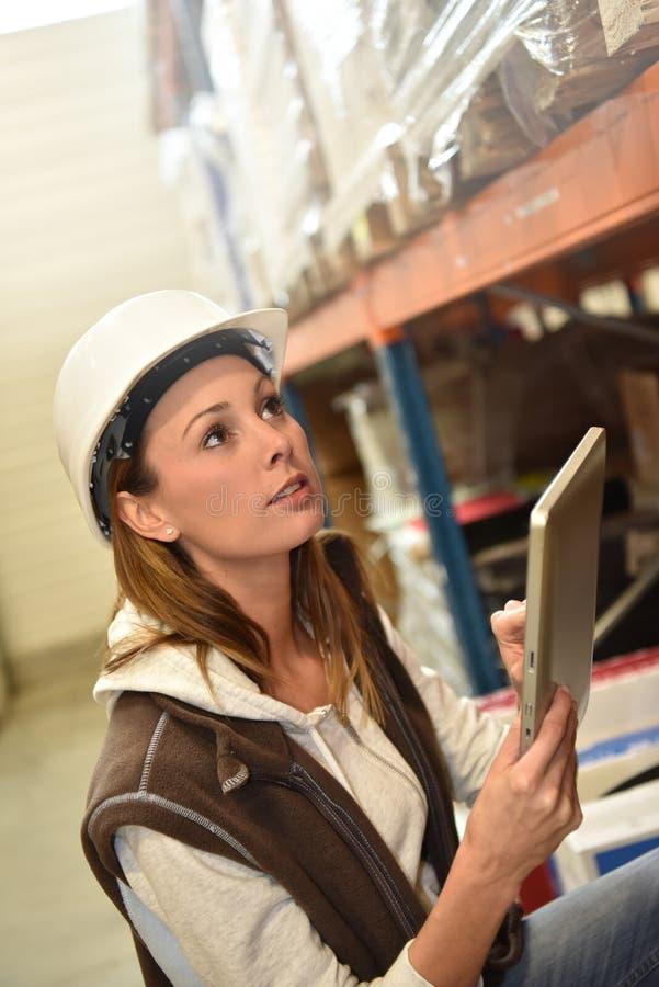 Lagerchef som kontrollerar materielet i lager royaltyfri fotografi