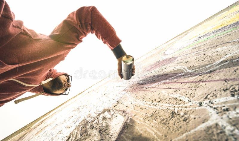 Lagere mening van straatkunstenaar het schilderen graffiti op generische muur stock foto