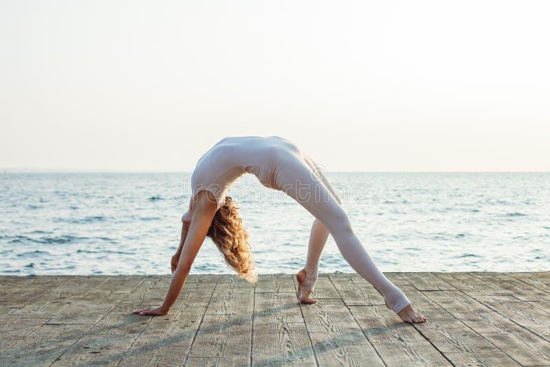 Lagerföra fotoet av den unga Caucasian kvinnan som gör yoga vid havet under solnedgången royaltyfria foton