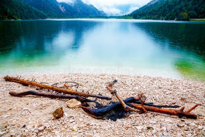 Lagerfeuer auf dem Ufer von See See mit Berg im Sommerregen stockbilder
