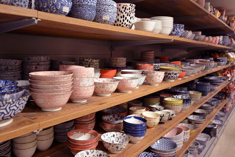 Lagerhylla med traditionell asiatisk bordsservis som keramisk risbunkar eller soppadisk arkivbild