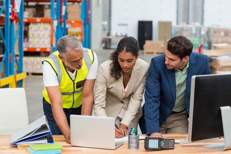 Lagermanager und -arbeitskraft, die mit Laptop sich besprechen stockbild