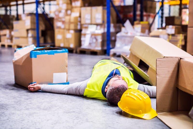 Lagern Sie Arbeitskraft nach einem Unfall in einem Lager ein lizenzfreie stockfotografie