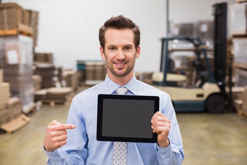 Lagern Sie den Manager ein, der den Tabletten-PC zeigt, der an der Kamera lächelt stockbilder