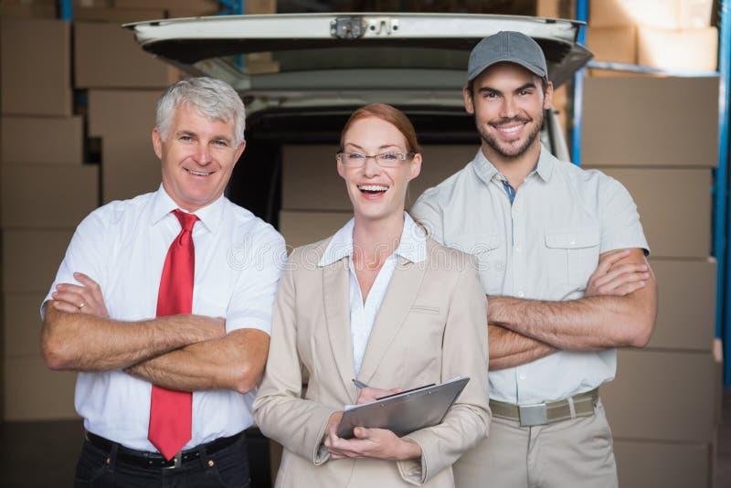 Lagern Sie die Manager und Lieferungsfahrer ein, die an der Kamera lächeln stockbild