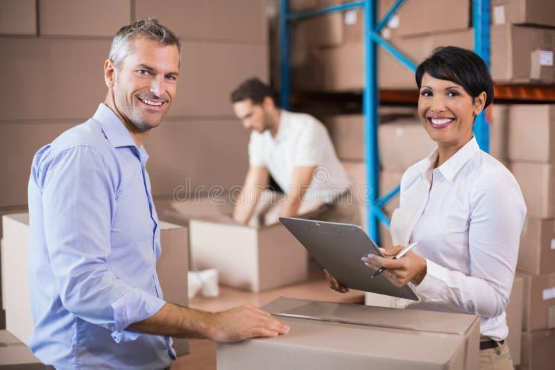 Lagern Sie Managerschreiben auf dem Klemmbrett ein, das mit Kollegen spricht stockbild