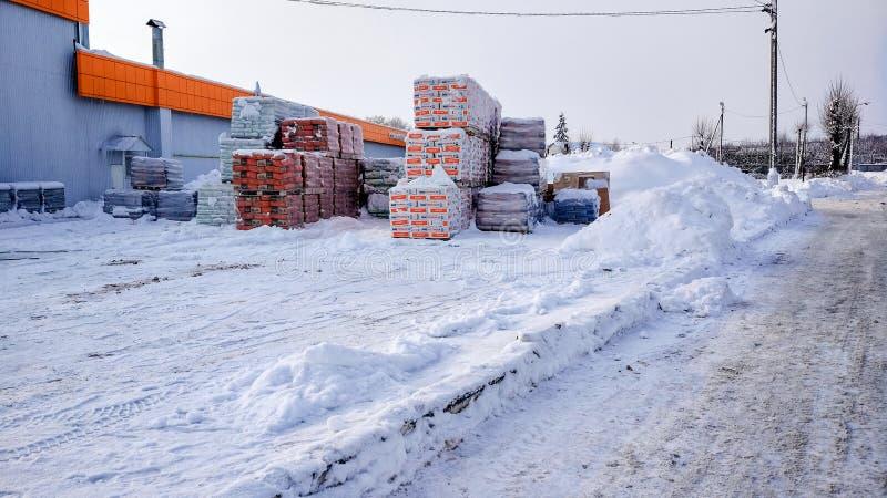 Lagern Sie Speicher im Freien im Winter in der Stadt ein Säcke mit Zement und Kitt auf einer hölzernen Palette, für an sich öffne lizenzfreies stockfoto