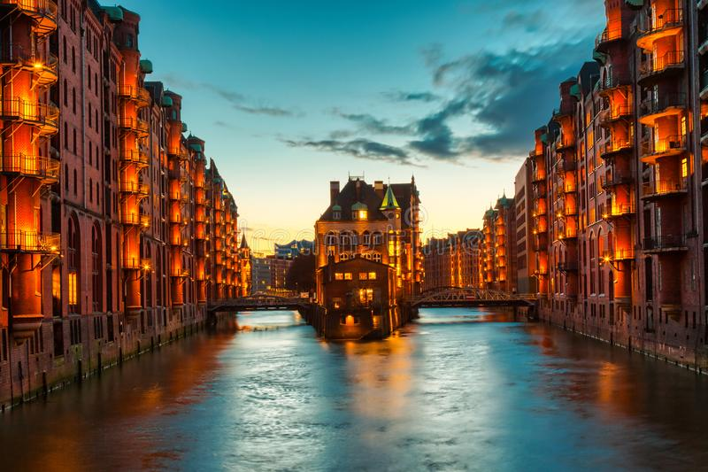 Lageromr?det Speicherstadt under skymningsolnedg?ng i Hamburg, Tyskland Upplysta lager i den Hafencity fj?rdedelen in royaltyfri bild