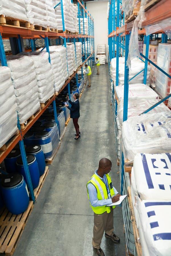 Lagerpersonal som kontrollerar materiel i lager arkivfoto