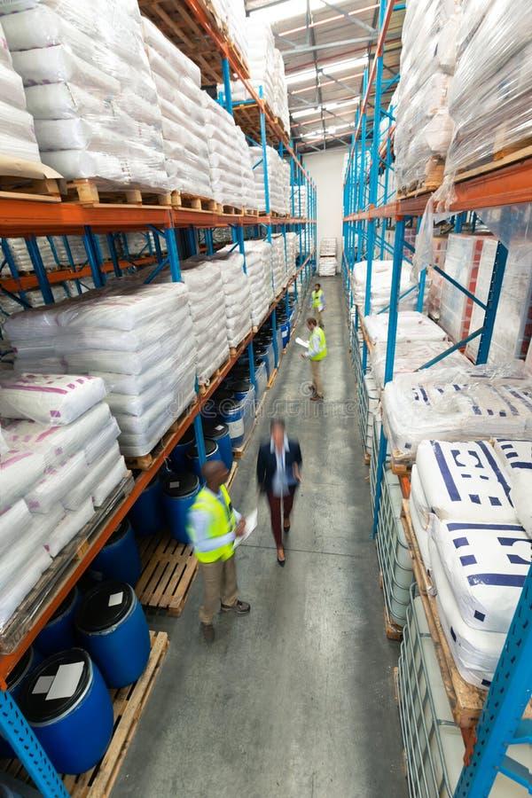 Lagerpersonal som kontrollerar materiel i lager fotografering för bildbyråer