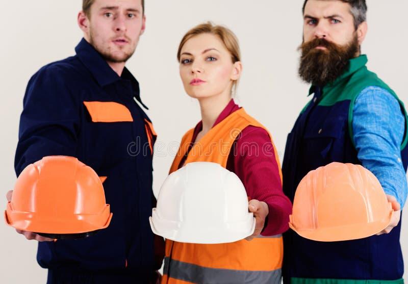 Laget av arkitekter, byggmästare, teknikerer visar hjälmar isolerad vit bakgrund som är defocused Män och kvinnan bär likformign royaltyfria foton