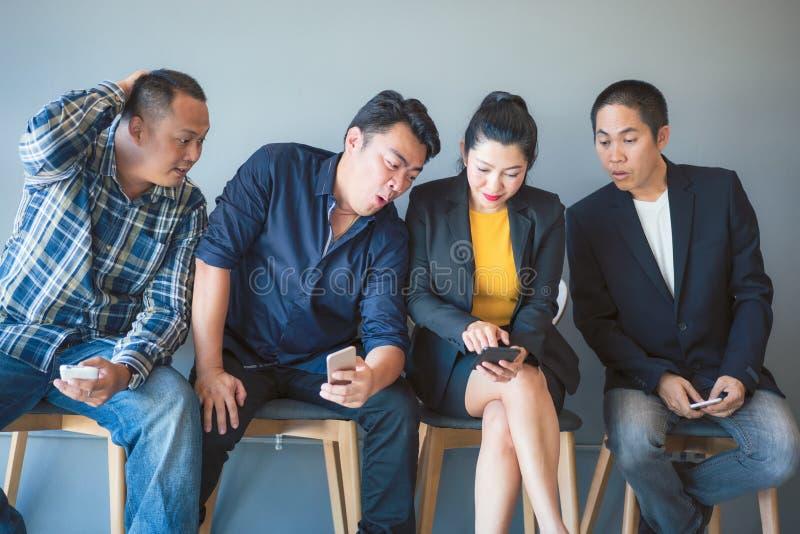 Laget av asiatiskt folk för affären upphetsas om informationen på smartphonen av gruppmedlemmarna, medan vänta på ett jobb royaltyfria bilder