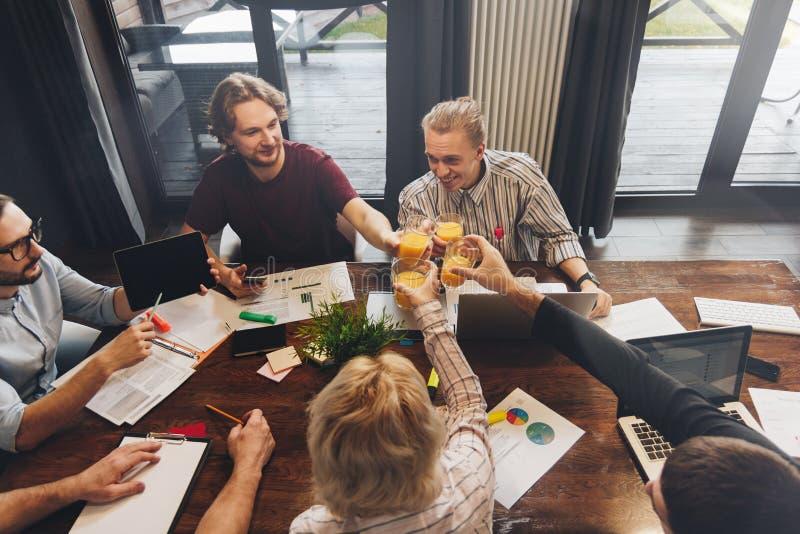 Laget av coworkers sitter runt om en trätabell- och affärsdocume arkivbild