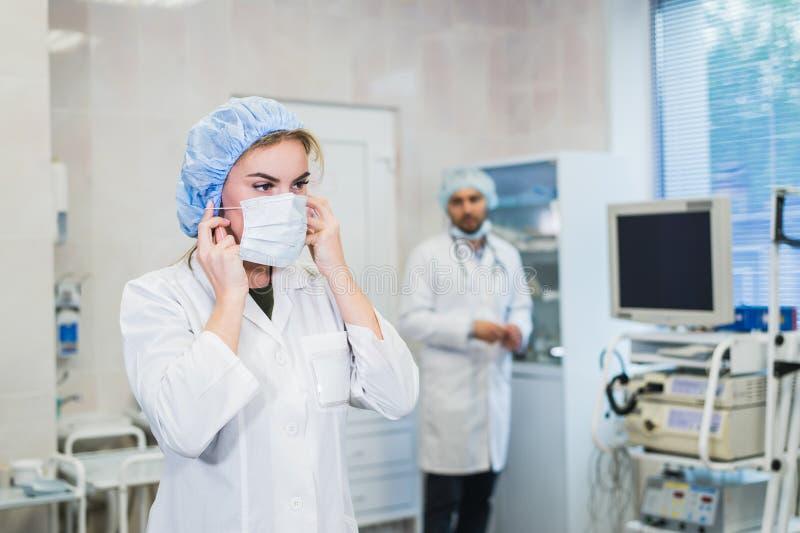 Laget av doktorer är förberett för operationen Den bärande maskeringen för sjuksköterskaassistent Doktor som förbereder utrustnin royaltyfri foto