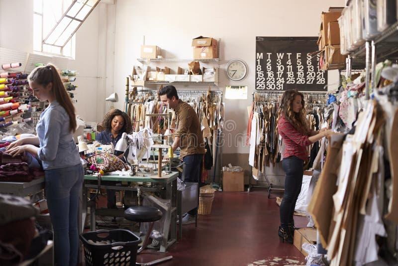 Laget av folk som tillsammans arbetar i kläder, planlägger studion royaltyfri foto