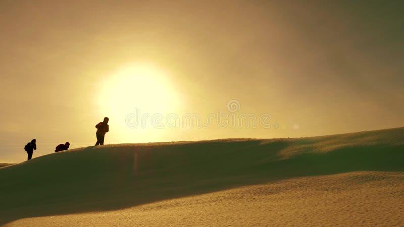 Laget av handelsresande följer sig längs snökant mot bakgrunden av den gula solnedgången koordinerad teamwork av turister royaltyfria bilder
