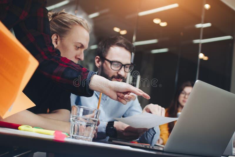 Laget av unga chefer arbetar i ett modernt kontor på en trätabl arkivbilder