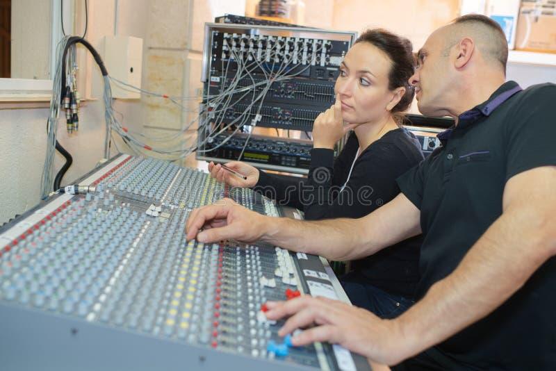 Laget iscensätter arbete på det blandande skrivbordet i inspelningstudio arkivbild