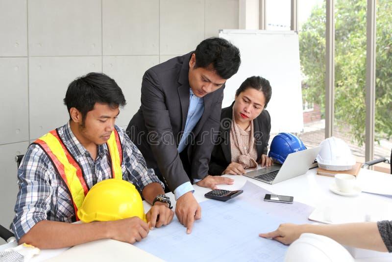 Laget iscensätter funktionsduglig mötesrum på kontoret Tre arbetare talar konstruktionsplan Elektrikersnickare eller Technica arkivbilder