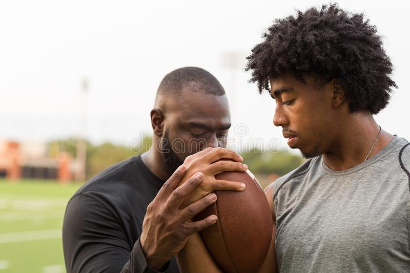 Lagledare f?r amerikansk fotboll som utbildar en ung idrottsman nen royaltyfria foton