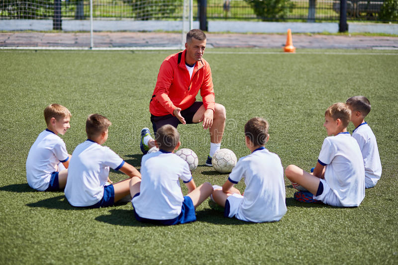 Lagledare Instructing Junior Football Team i praktiken royaltyfri bild