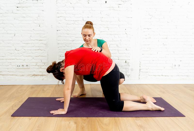 Lagledareinstruktören som undervisar den unga kvinnan att sträcka tillbaka i pilatesyogako, poserar i sund livsstil royaltyfria bilder