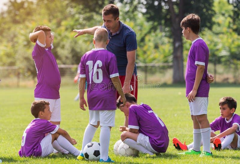 Lagledaren ger rådgivning till fotbollspelare på fotbollsmatch arkivbild