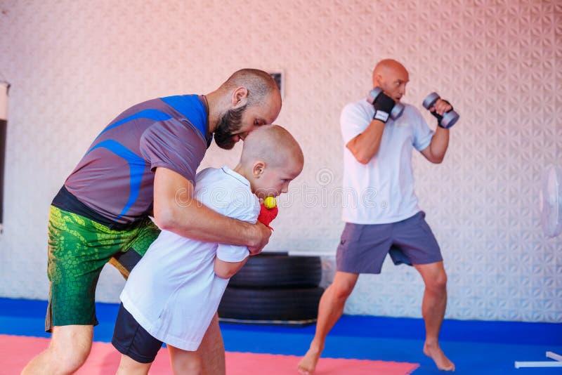 Lagledaren undervisar pojkesparkboxningen royaltyfri foto