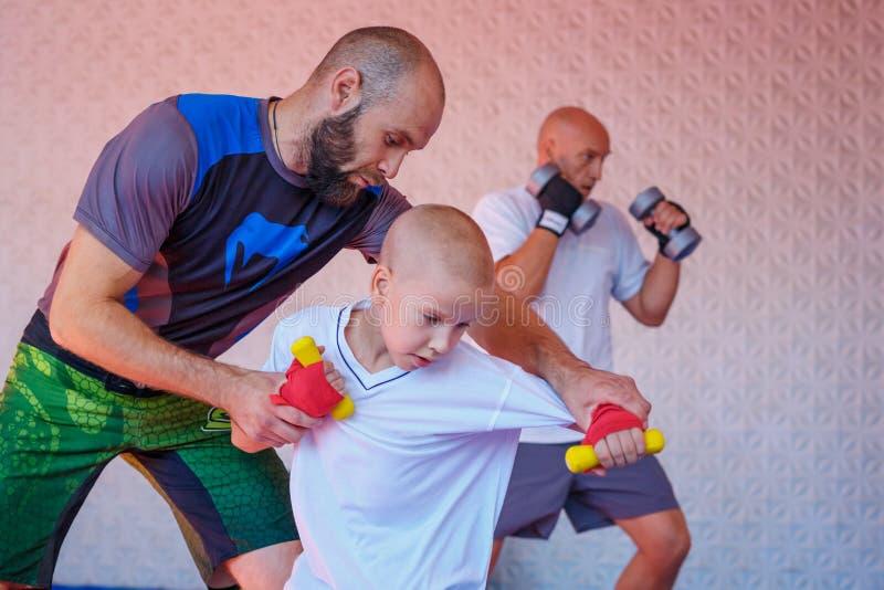 Lagledaren undervisar pojkesparkboxningen royaltyfri bild