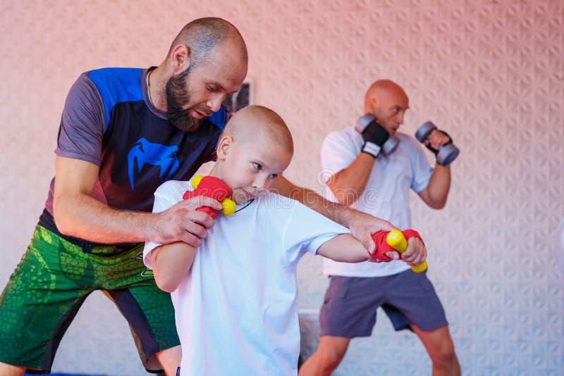 Lagledaren undervisar pojkesparkboxningen royaltyfria bilder
